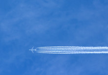 Airplane With Contrails In Clear Blue Sky, Cruising Altitude