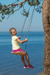 little girl swinging on seesaw above a sea sunrise