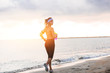 Young fit girl running on beach at sunrise