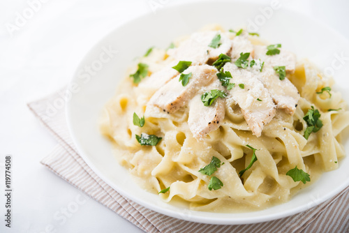Pasta fettuccine alfredo with chicken, parmesan and parsley on white background close up Canvas Print