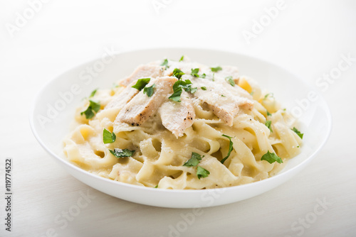 Photo Pasta fettuccine alfredo with chicken, parmesan and parsley on white background close up