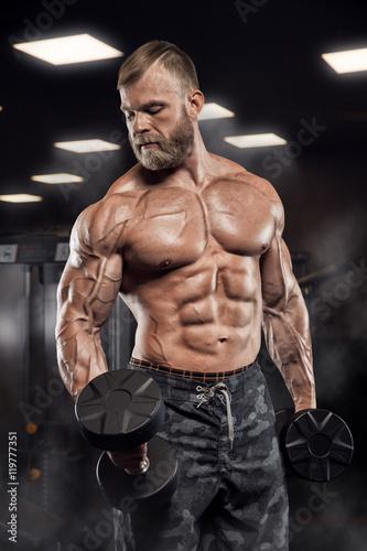 Fotografie, Obraz  Muscular athletic bodybuilder fitness model posing after exercises in gym