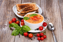 Fresh Bowl Of Creamy Tomato Soup And Sandwich With Basil Leaves