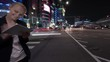 Timelapse panning and wide angle shot of young woman using touch pad on the busy street of night Seoul city in Republic of Korea. Illuminated buildings, motorway with car traffic and pedestrian