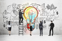 Business Team Near Blackboard With Light Bulb Sketch