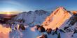 Snowy mountains under orange sunset sky