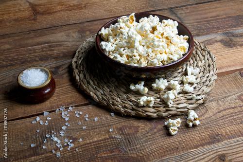Fotografie, Obraz  Miska z popcornem na drewnianym tle