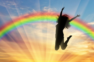 Happy woman jumping near rainbow