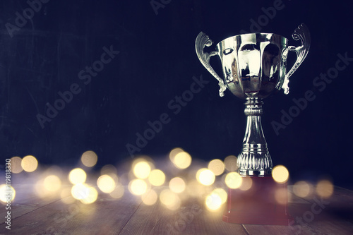 Photo low key image of trophy over wooden table
