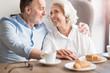 Joyful loving couple sitting at the table