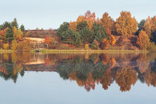 Foggy Morning Over The Lake, Fall Trees Reflected In Water.
