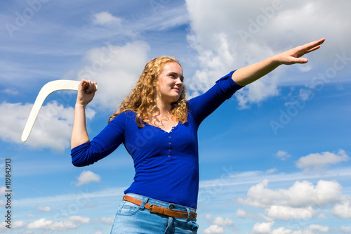 фотография  Young caucasian woman throwing boomerang
