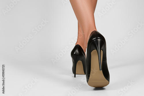 Stampa su Tela Low view of female legs in high heel shoes. Back view of walking