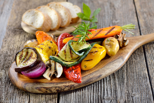Staande foto Grill / Barbecue Vegan grillen: Gemischtes Gemüse vom Grill mit Kräutern, Gewürzen und Olivenöl, dazu frisches Ciabattabrot - Mixed grilled vegetables on a wooden cutting board served with Italian ciabatta bread