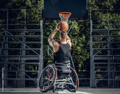 Valokuva  Cripple basketball player in wheelchair plays basketball.