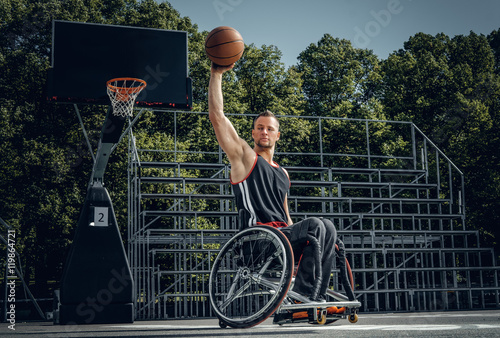 Foto  Cripple basketball player in wheelchair plays basketball.