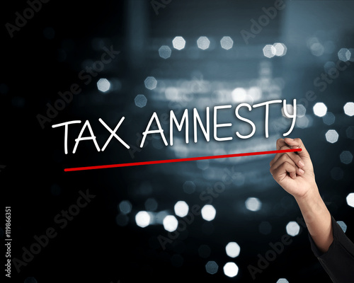 Photo Hand holding pen and write tax amnesty words, sparks light background
