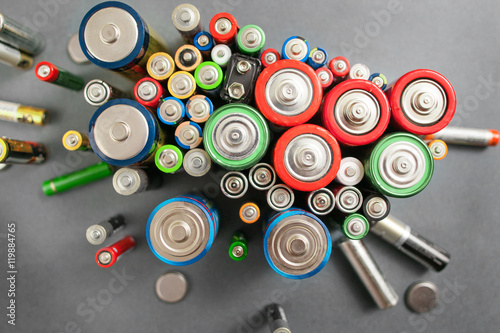 Fotografie, Obraz Selection of different batteries, top view on colorful commercial accumulators on gray background