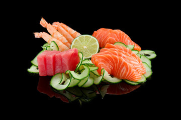 Panel SzklanySashimi set (shrimp, salmon,tuna) with lime and cucumber over black background.