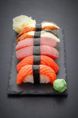 FototapetaSushi nigiri set on a stone plate over black background