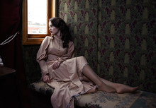 Young Woman In Beige Vintage Dress Of Early 20th Century Sitting