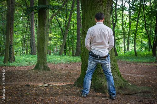 Standing man peeing near big tree in summer forest Fototapeta