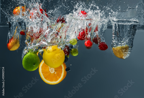 Fototapeten Wasserfalle Different fruits and berries falling in water on dark background