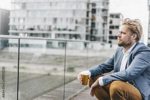 Businessman sitting on bridge having coffee break