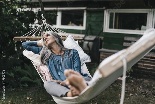 Pensive woman lying in hammock in the garden