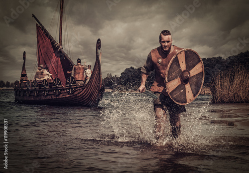 Viking warrior in the attack, running along the shore with Drakkar on the background Canvas Print
