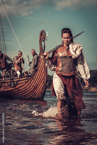 Viking woman with sword walking along the shore with Drakkar on the background. Wall mural