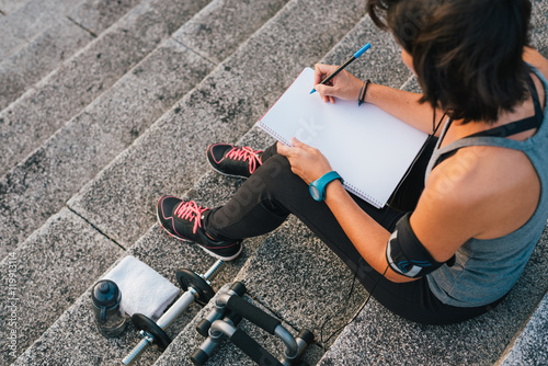Photo  Fitness sporty woman writing on blank notepad while sitting on urban stone stairs before exercises workout routine