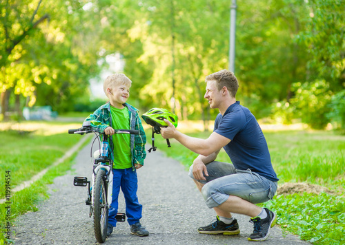 Fotografía  father talking with his son riding a bicycle