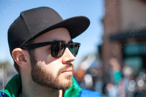 e29d813da945 Portrait of young handsome man with black beard wearing dark sunglasses,  cap and blue sleeveless
