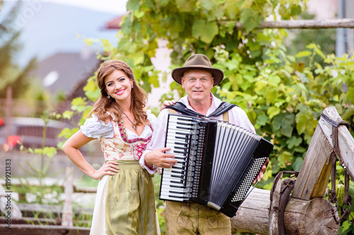 Fotografía  Couple in traditional bavarian clothes with accordion, green gar