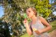 little girl blowing soap bubbles in summer park