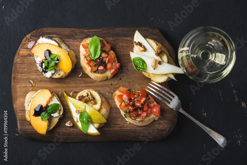 Photo sur Toile Entree Bruschetta set with glass of white wine. Black plywood background, top view, horizontal composition
