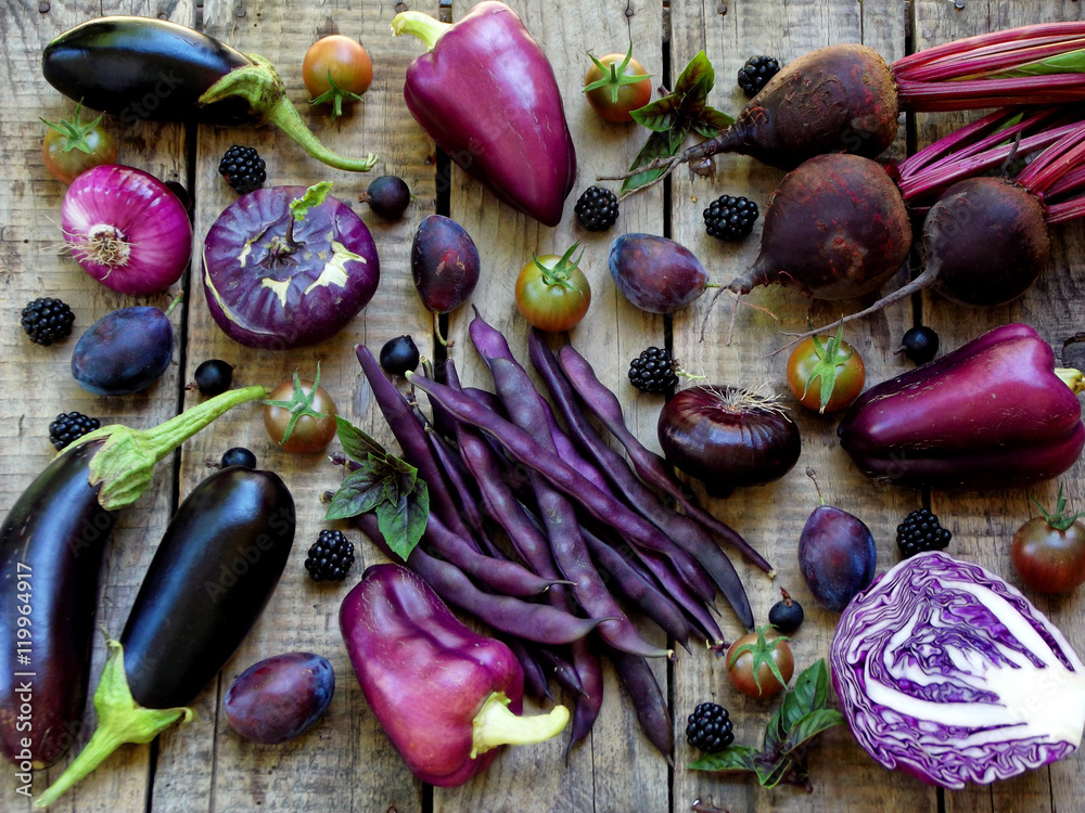 purple vegetables and fruits on wooden background - eggplant, cauliflower, green beans, cherry tomatoes, plum, basil, onion, cabbage, sweet pepper