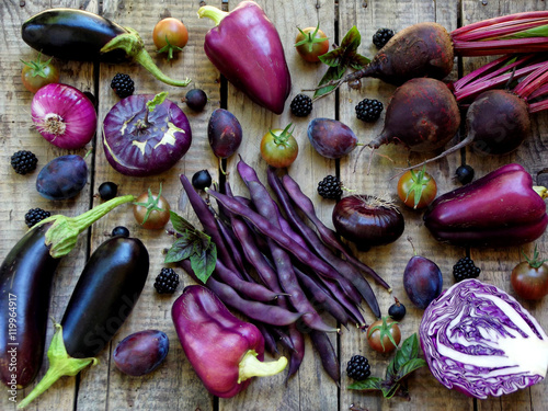 Staande foto Groenten purple vegetables and fruits on wooden background - eggplant, cauliflower, green beans, cherry tomatoes, plum, basil, onion, cabbage, sweet pepper