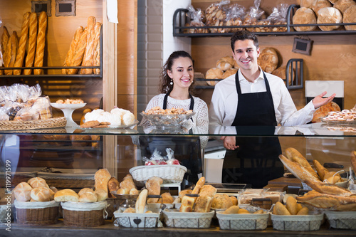 Foto op Canvas Bakkerij Smiling couple selling pastry and loaves