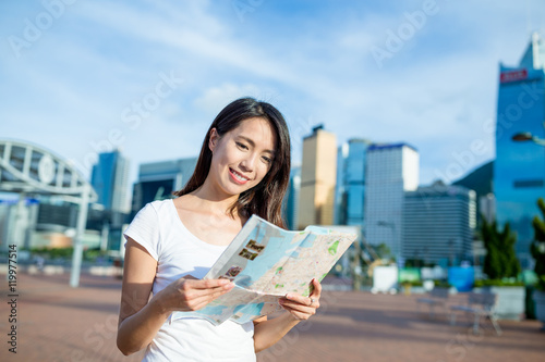 Woman reading on paper map Poster