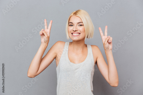 Foto  Cheerful cute young woman showing peace sign with both hands
