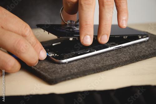 Fotografía  Man uses vacuum plug and plastic opener to change screen from broken phone, his