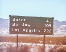 California Road Sign Los Angeles Baker Barstow. California Highway Sign Showing Mileage To The Cities Of Baker, Barstow And Los Angeles. Shot In The Mohave Desert Along Interstate Highway 15.