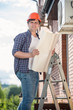 Electrician standing on high stepladder and holding plan of hous
