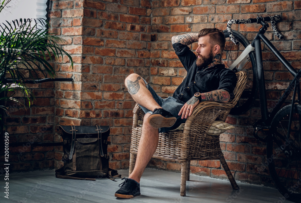 Fototapeta The bearded hipster male relaxing in a chair.