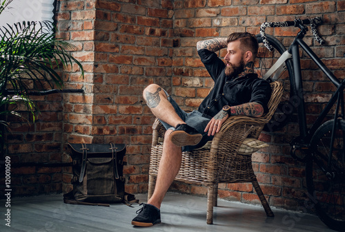 The bearded hipster male relaxing in a chair. Slika na platnu