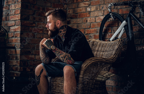 Carta da parati  The bearded hipster male relaxing in a chair.