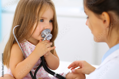 Fotografia  Happy little girl at  health exam at doctor's office