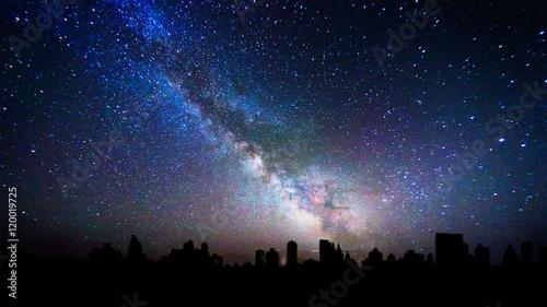 Milky way galaxy over a city skyline silhouette